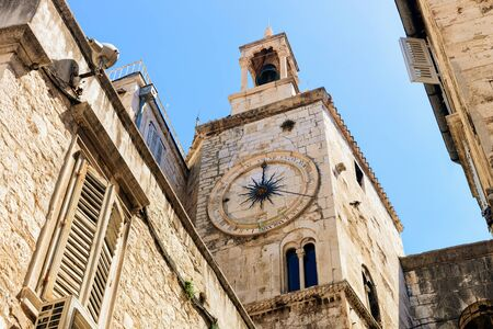 Famous clock tower in Street in Old city of Split on Adriatic Coast in Dalmatia in Croatia. Roman architecture of Belfry at Diocletian Palace in Dalmatian Town. Window with shutters on background