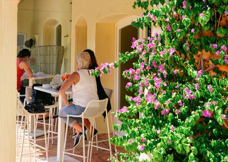 People at Street cafe with tables and chairs in Porto Cervo luxury resort city in Sardinia Island in Italy in summer. Cozy restaurant with tourists, Sardegna