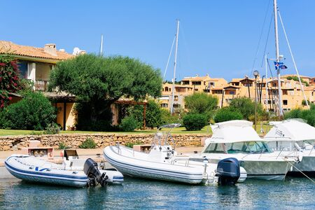 Marina and luxury yachts near Mediterranean Sea in Porto Cervo in Sardinia Island in Italy in summer. View on Sardinian town port with ships and boats in Sardegna. Zdjęcie Seryjne