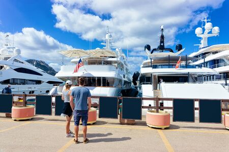 Couple at Marina with luxury yachts in Mediterranean Sea in Porto Cervo in Sardinia Island in Italy in summer. View on Sardinian town port with ships and boats in Sardegna. Zdjęcie Seryjne
