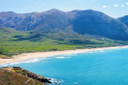 Beach at the Mediterranean Sea at Buggerru in South Sardinia in Italy. Sardinian Italian resort with yellow sand in Sardegna.