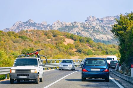 Car with bicycle in the road in Costa Smeralda in Sardinia Island in Italy in summer. Transport driving on the highway in Europe. View on motorway. Stock fotó