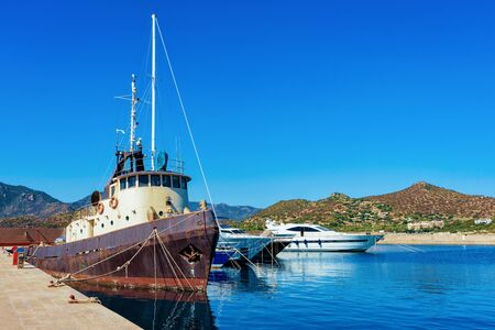 Sardinian Port and marina with Old ship at Mediterranean Sea in city of Villasimius in South Sardinia Island in Italy in summer. Cityscape with Yachts and boats Zdjęcie Seryjne