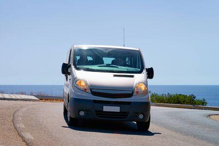 Mini van in the Road in Villasimius in Cagliari in Sardinia Island in Italy. Mediterranean Sea on the background.