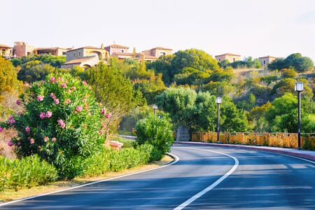 Empty road without cars in Porto Cervo luxury resort in Sardinia Island in Italy in summer. Panorama with highway and green nature and blue sky.