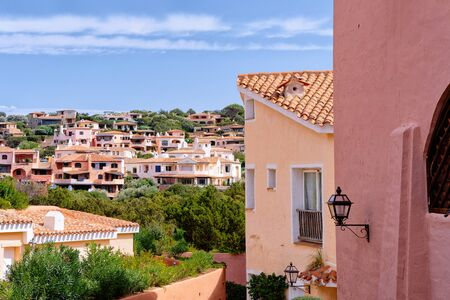 View on of residential house complex. Apartment flat building. Coastal home architecture in Porto Cervo luxury resort city in Sardinia Island in Italy in summer. View on Sardinian town in Sardegna.