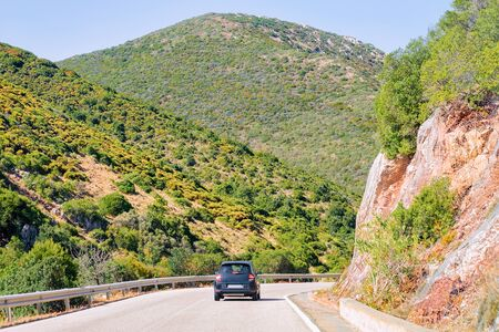 Scenery with the car in the highway in Carbonia near Cagliari in Sardinia in Italy. Nature and Automobile back in the road. Mountains and hills on the background Stock fotó