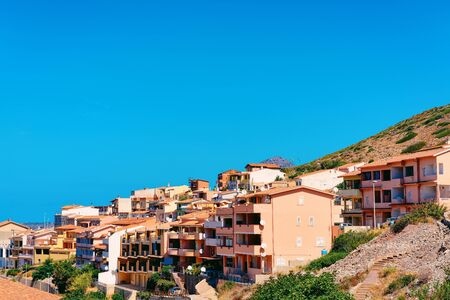 Buggerru city with houses architecture at the hills of the Mediterranean Sea in South Sardinia in Italy. Sardinian Italian small town with buildings in Sardegna. Stock fotó