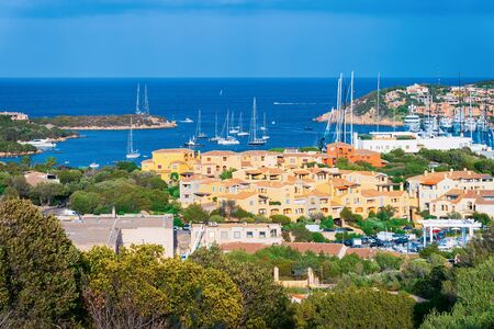 scenery with Marina and luxury yachts at Mediterranean Sea in Porto Cervo in Sardinia Island in Italy in summer. View on Sardinian town port with ships and boats in Sardegna.