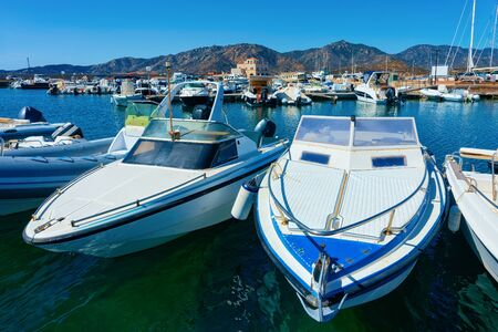 Old Sardinian Marina with ships in Mediterranean Sea in city of Villasimius in South Sardinia Island in Italy in summer. Cityscape with port and Yachts and boats