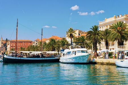 Ships at Palm trees at Old city of Split on Adriatic Coast in Dalmatia in Croatia. Diocletian Palace and Roman Town architecture at Croatian Dalmatian Bay. Europe tourism and vacation in summer.
