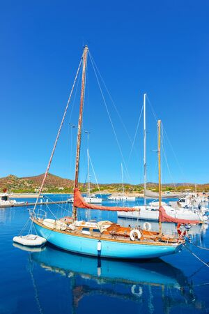 Old Sardinian Marina with ships at Mediterranean Sea in city of Villasimius in South Sardinia Island in Italy in summer. Cityscape with port and Yachts and boats