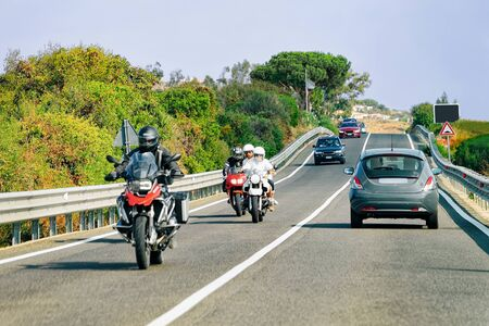 Motorcycles and cars in the road in Costa Smeralda in Sardinia Island in Italy in summer. Motorcyclist driving scooter on the highway in Europe. View on moped on motorway.