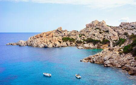 Boats in the Mediterranian Sea near mountains in Capo Testa in Santa Teresa Gallura, Sardinia, Italy. Ship and blue water. Foto de archivo - 129523386