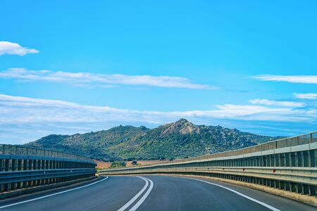 Empty road without cars at Sardinia Island in Italy in summer. Panorama with highway and green nature and blue sky. Mountains on the background. Foto de archivo - 129523805