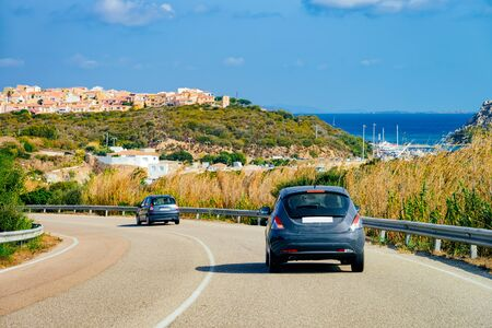 Cars in the road at Porto Cervo in Costa Smeralda in Sardinia Island in Italy in summer. Transport driving on the highway in Europe. View on motorway. Foto de archivo - 129523840
