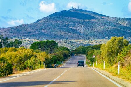 Car on the road in Costa Smeralda in Sardinia Island in Italy in summer. Transport driving on the highway in Europe. View on motorway. Hills and mountains on the background Foto de archivo - 129524010