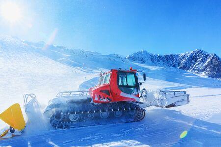 Ratrack machine making ski piste in Hintertux Glacier ski resort in Zillertal in Tyrol in Austria in winter in Alps. Alpine mountains with snow. Ratrac in Downhill. Blue sky and white slopes. Foto de archivo - 129524028