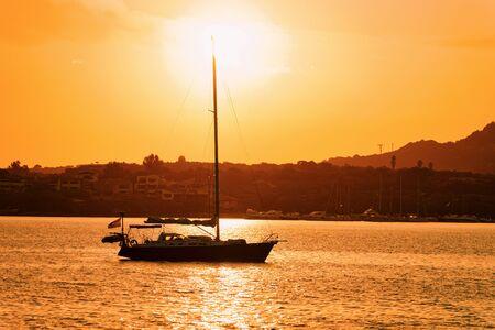 Sunrise or sunset with yacht at Porto Rotondo in Costa Smeralda at Mediterranean sea in Sardinia island in Italy. Boat in Sardegna in summer. Foto de archivo - 129524893