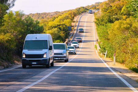 Mini van on the road in the street of Costa Smeralda on Sardinia Island in Italy in summer. Minivan transport in Europe. View on highway. Foto de archivo - 129524922