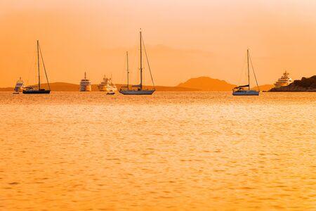 Sunrise or sunset with yachts in Porto Rotondo in Costa Smeralda at Mediterranean sea in Sardinia island in Italy. Boat in Sardegna in summer. Foto de archivo - 129524931