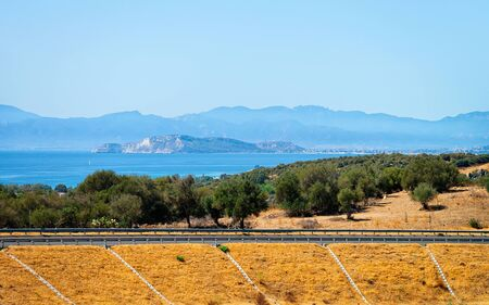 Empty road without cars in Sardinia Island in Italy in summer. Panorama with highway and green nature and blue sky. Mediterranean sea on the background. Foto de archivo - 129524936