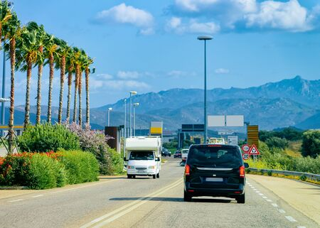 Car minivan and Rv cavaran on the road in Costa Smeralda on Sardinia Island in Italy in summer. Motorhome rving on motorway. Camper trailer on highway. Palm trees Foto de archivo - 129524953