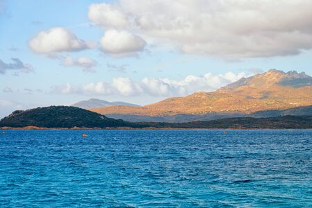 Mediterranean sea on Capriccioli Beach of Costa Smeralda on Sardinia island in Italy. Sky with clouds