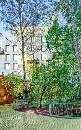 Europe Birch trees and Modern glass residential building. And outdoor facilities.