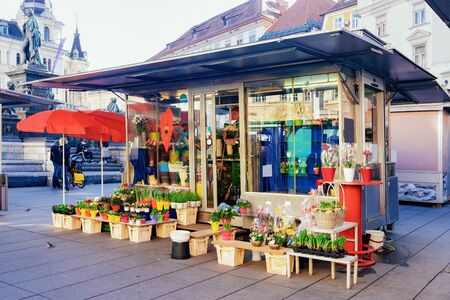 Flower shop with spring flowers on display on Hauptplatz at Rathaus Town Hall in Downtown and Old city of Graz in Austria. Kiosk in street market in Town in Styria in Europe. Imagens