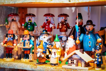 Wooden Christmas tree toys in Christmas market in Germany in Europe in winter. German Night street Xmas and holiday decorations fair in European city or town, December. Berlin in Gendarmenmarkt Stock Photo