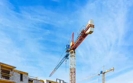 Construction of apartment house and home residential building real estate concept. Lifting cranes and blue sky