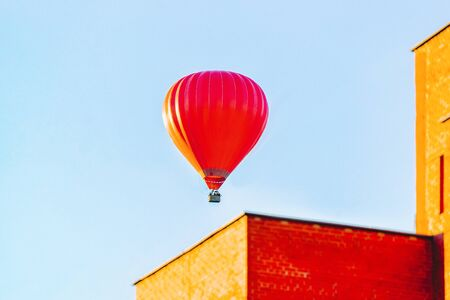 Red air balloon flying over the residential house building in the city