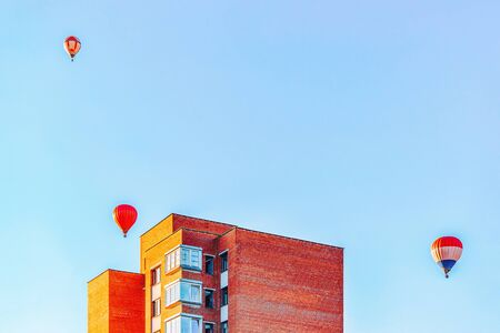 Red air balloons flying over the residential house building in the city