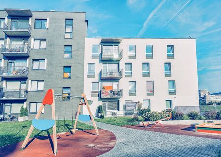 Complex of new apartment  buildings with children playground as outdoor facilities.