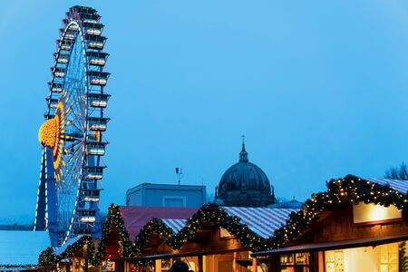 Christmas market with Ferris Wheel in Germany in Europe in winter. German Night street Xmas and holiday fair in European city or town. On Berliner Rathaus 写真素材