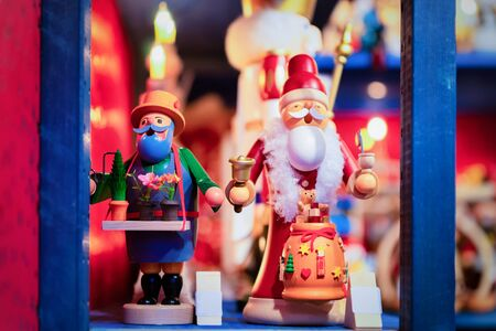 Wooden Christmas tree toys and Santa Claus in Christmas market in Germany in Europe in winter. German Night street Xmas and holiday decorations fair in European city or town. Berlin in Gendarmenmarkt Stock Photo