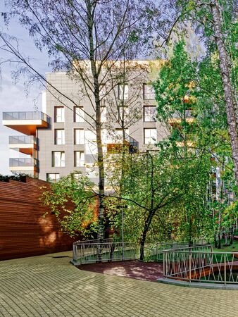Birch trees and Modern glass residential building. And outdoor facilities.