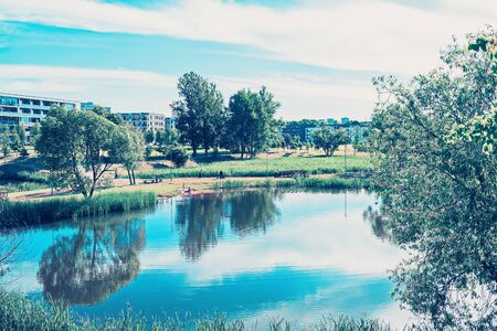 Landscape with park and pond and modern apartment buildings on the background