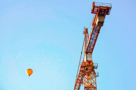Lifting crane and hot air balloon on development site in the blue sky