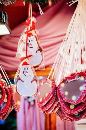 Heart shape Gingerbread cookies on Christmas market of Germany in Europe in winter. German Night street Xmas and holiday fair in European city or town, December. Kaiser Wilhelm Memorial Church, Berlin