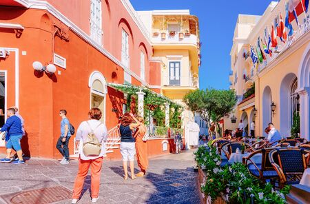 Capri, Italy - October 3, 2017: People in Street cafe and restaurant table and chair on Capri Island, Naples, Italy. Landscape with Cafeteria, Italian coast. Anacapri in Europe. View in summer. Amalfi