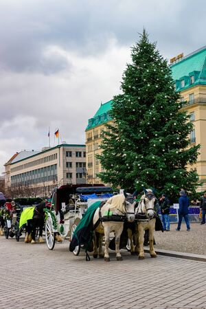 Berlin, Germany - December 8, 2017: Carriage with horses on Pariser Platz at Brandenburg gate and Street with Christmas tree in German City centre in Berlin in Germany in Europe. Brandenburger tor.