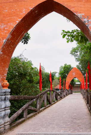 Bridge with flags at My Son Sanctuary and Hindu Temple near Hoi An in Vietnam in Asia. Heritage of Champa Kingdom. Myson History and Culture. Shiva city ruins. Vietnamese Museum.
