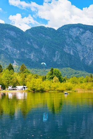 Landschaft mit Camping von Wohnwagenanhängern, Paragliding und Kanu am Bohinj-See in Slowenien. Natur- und Wohnmobile in Slowenien. Blick auf Wohnmobil und Berge. Landschaft Standard-Bild