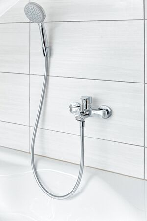 Shower head and metal tap Modern in white Bathroom. Design of luxury interior of home house or hotel room. Clean white tile on background. New Toilet furniture with top decor..