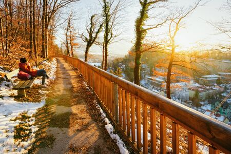 Panorama of sunset at Salzburg with snow from Monchsberg hill in Austria. Girl sitting on bench. Landscape and cityscape of Mozart city in Europe at winter. Panoramic view. Scenery with sun flare. Stock Photo