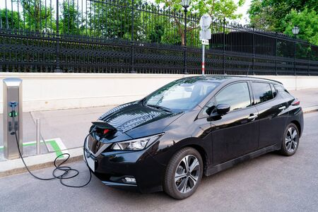 Electric Car Charging station at Vienna, Austria. Battery hybrid vehicle eco charger. Future energy power. Green technology. Transport and plug. Fuel recharge. Clean ecology concept. Modern black car Archivio Fotografico