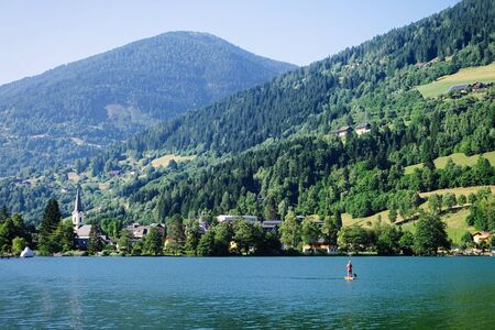 Panorama of lake Field am See in Carinthia, Austria. Landscape with pond and blue sky in spring or summer. Scenery in green Alps of Europe. Countryside with Alpine mountains. Nature with water