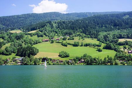 Panorama of lake Field am See of Carinthia in Austria. Landscape with pond and blue sky in spring or summer. Scenery in green Alps of Europe. Countryside with Alpine mountains. Nature with water
